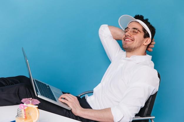 Portrait de mec joyeux à lunettes, casquette blanche et chemise souriant et tenant un ordinateur portable.