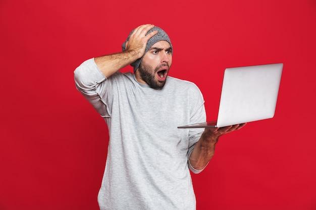Portrait de mec mécontent de 30 ans en tenue décontractée en saisissant la tête tout en tenant un ordinateur portable en argent isolé