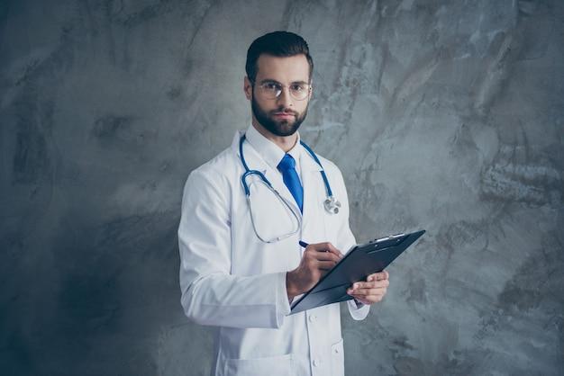 Portrait de mec médecin concentré tenir son presse-papiers écrire les plaintes des patients portent un manteau médical blanc isolé sur un mur de couleur grise