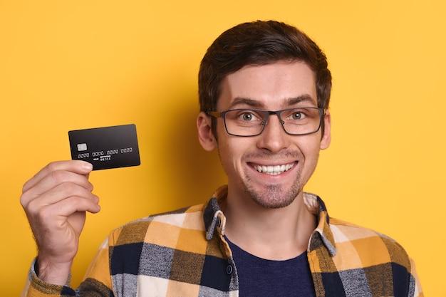 Portrait d'un mec souriant heureux dans des verres portant des vêtements décontractés tenant une carte de crédit