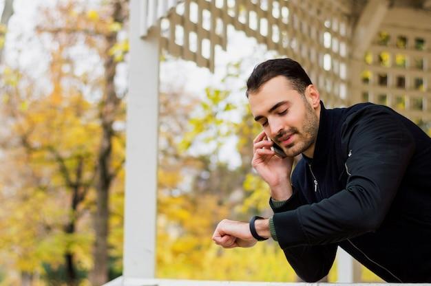 Portrait d'un mec souriant parlant au téléphone mobile à l'extérieur.