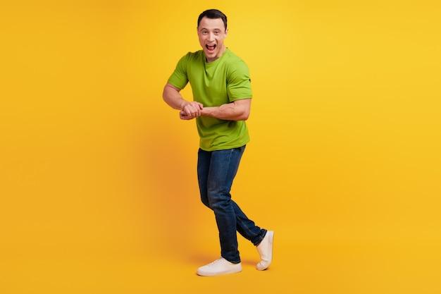 Portrait d'un mec sportif brutal et fou qui montre les mains du biceps sur le mur jaune