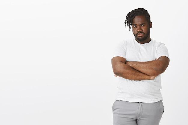 Portrait de mec suspect avec des tresses posant contre le mur blanc