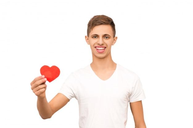 Portrait d'un mec en t-shirt blanc tenant un coeur, isoler