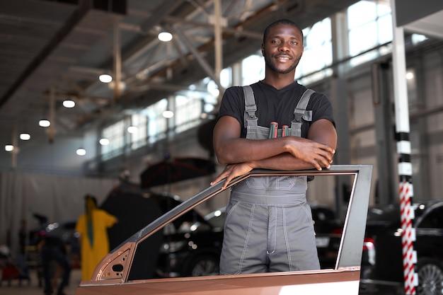 Portrait de mécanicien automobile afro-américain positif en uniforme posant après le travail