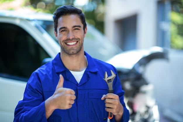 Portrait de mécanicien heureux avec une clé montrant les pouces vers le haut