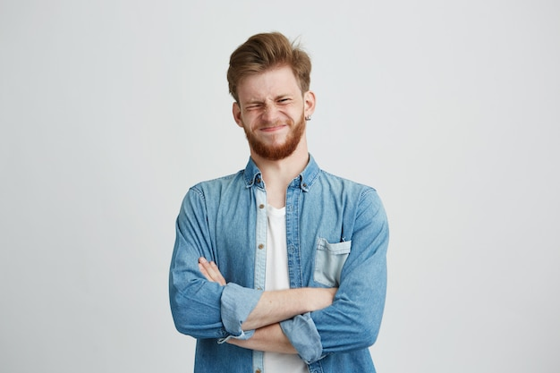 Portrait de méchant jeune bel homme en chemise en jean avec les bras croisés.