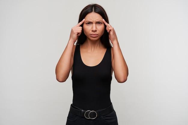 Portrait de mécontent froncement de sourcils jeune dame aux cheveux noirs keepig index sur ses tempes tout en regardant avec les lèvres pliées, souffrant de maux de tête, isolé