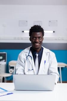 Portrait d'un médecin afro-américain assis au bureau dans le cabinet