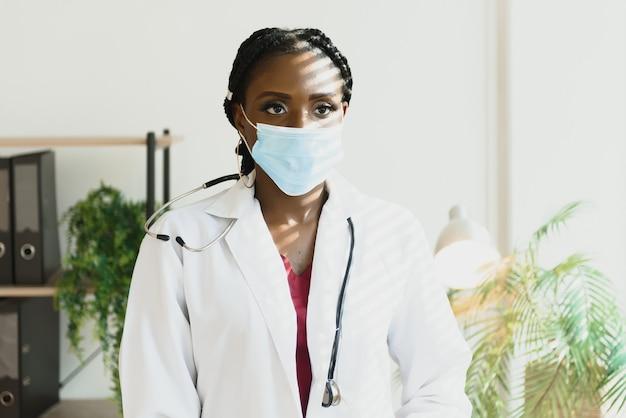 Portrait d'un médecin afro-américain en robe blanche et masque facial