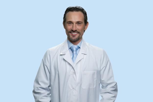 Portrait d'un médecin d'âge moyen souriant en blouse blanche. isolé sur fond bleu.