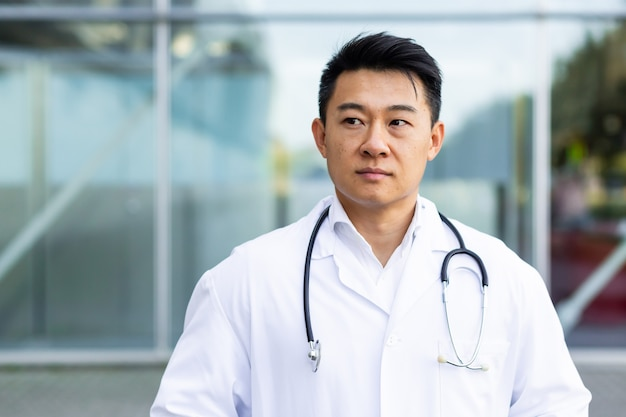 Portrait d'un médecin asiatique sévère et sérieux sur le fond d'une clinique extérieure moderne