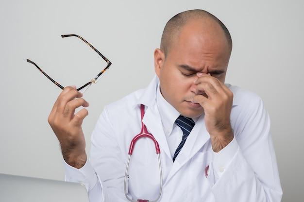 Un portrait de médecin asiatique avec stéthoscope se frottant les yeux