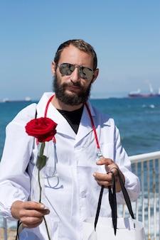 Portrait de médecin en blouse blanche avec stéthoscope et lunettes de soleil tenant une fleur rose rouge à la main. bel homme barbu américain sur fond de ciel bleu. le concept de récupération, gratitude au docteur