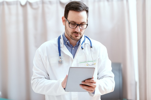 Portrait d'un médecin caucasien en uniforme et stéthoscope autour du cou à l'aide de la tablette. nouvelles technologies en médecine.