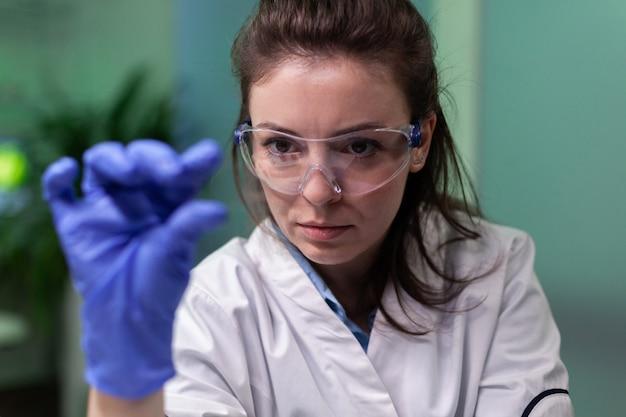 Portrait d'un médecin chercheur biologiste tenant une lame de microscope avec un échantillon de feuille verte découvrant des plantes génétiquement modifiées au cours d'une expérience biologique. chimiste travaillant dans le laboratoire de biochimie