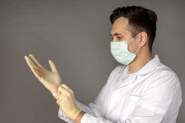 Portrait d'un médecin dans une robe médicale mettant des gants avant d'effectuer des tests pour le coronavirus