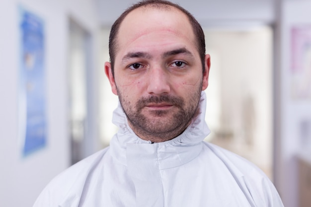 Portrait d'un médecin épuisé au bureau regardant la caméra portant un costume ppe sans écran facial assis sur une chaise dans une clinique de salle d'attente