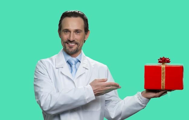 Portrait de médecin mature présentant une boîte cadeau rouge. isolé sur fond vert.