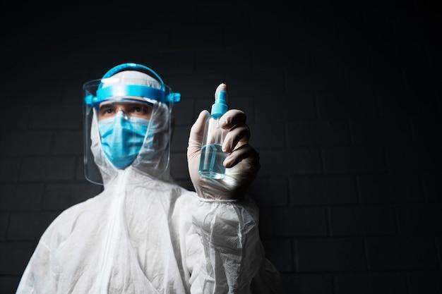 Portrait d'un médecin portant une combinaison epi contre le coronavirus et le covid-19, tenant un vaporisateur de bouteille de désinfectant sur fond noir avec espace de copie.