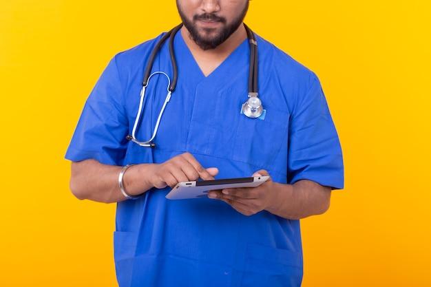 Portrait d'un médecin de race mixte avec un stéthoscope dans une robe bleue tenant une tablette. concept de site médical du médecin. copyspace