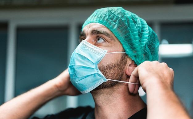 Portrait d'un médecin se préparant à travailler à l'intérieur de l'hôpital pendant la période de coronavirus - homme travailleur médical sur l'épidémie de covid-19 portant un masque de protection faciale