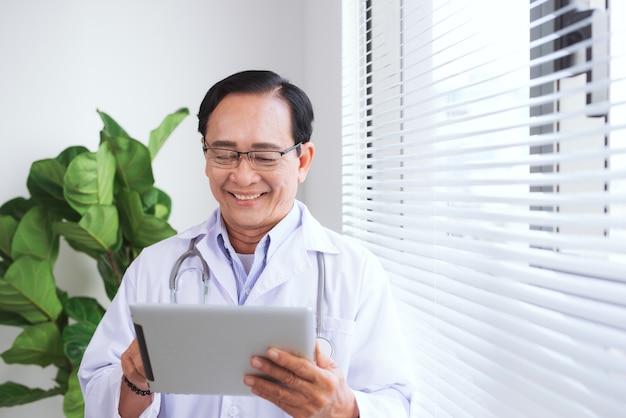 Portrait d'un médecin senior utilisant une table en se tenant debout dans un cabinet médical