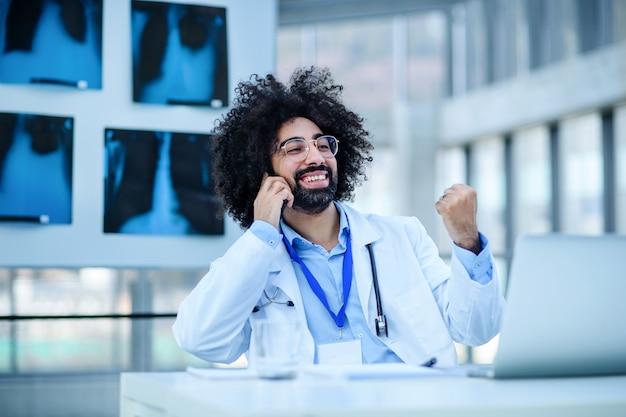 Portrait d'un médecin de sexe masculin joyeux assis à l'hôpital, utilisant un ordinateur portable et un smartphone.