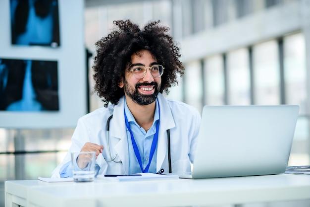 Portrait d'un médecin de sexe masculin joyeux et heureux assis à l'hôpital, utilisant un ordinateur portable.