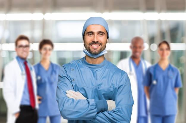 Portrait d'un médecin souriant devant son équipe