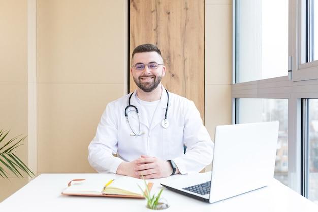 Portrait d'un médecin sympathique en uniforme avec ordinateur portable