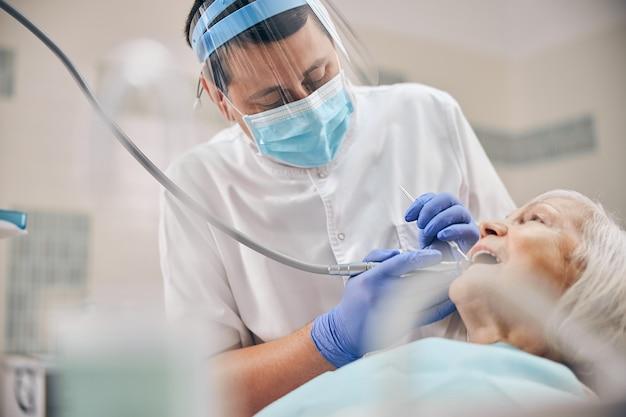 Portrait d'un médecin traitant des dents de femme avec des outils dentaires et un miroir avec une perceuse au carbone dans une clinique dentaire