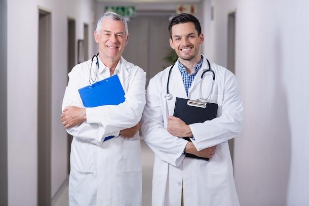 Portrait de médecins souriants debout avec presse-papiers