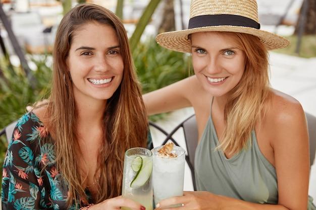 Portrait de meilleures amies à la recherche agréable ont une fête d'été, buvez des cocktails frais et froids. adorables lesbiennes tintent des verres de boisson, célèbrent le début des vacances