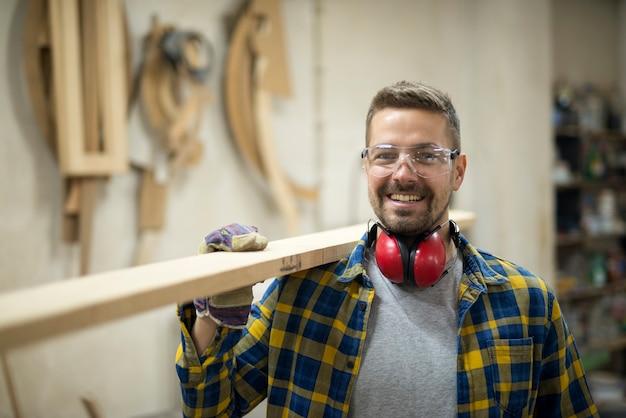 Portrait de menuisier souriant tenant une planche de bois à l'atelier de menuiserie.
