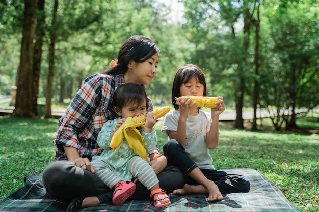 Portrait d'une mère accompagnant ses enfants mangent du maïs dans le jardin