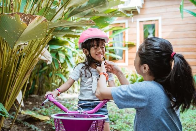 Portrait d'une mère aidant sa fille à porter un casque avant de faire du vélo