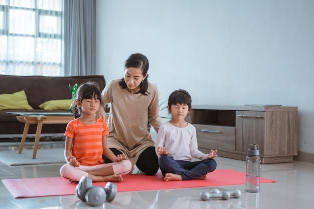 Portrait de mère aidant ses enfants à faire des exercices d'étirement à la maison ensemble