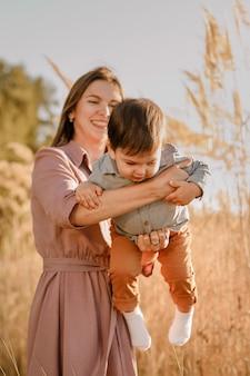 Portrait de mère aimante heureuse étreignant son bébé dans le parc ensoleillé près de la rivière