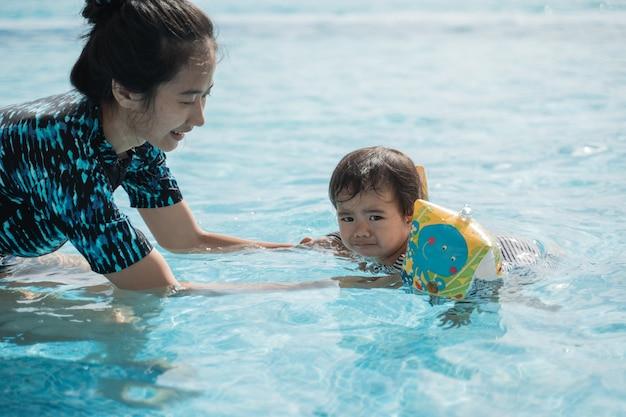 Portrait d'une mère apprenant à son enfant à nager dans la piscine dans la journée ensoleillée