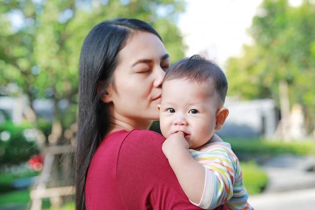Portrait de mère asiatique portant et embrassant son bébé bébé en plein air.