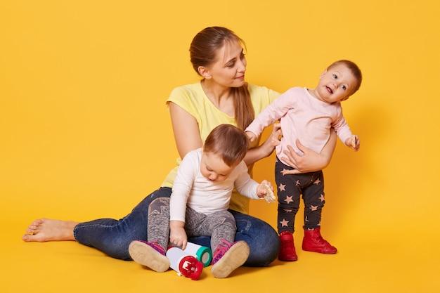 Un portrait d'une mère attentionnée active occupée avec ses enfants doux et bruyants