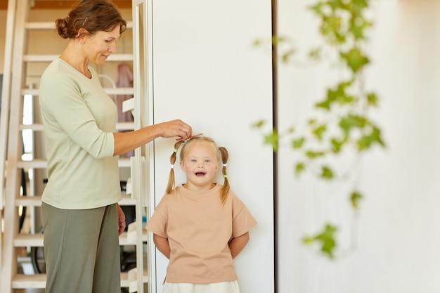 Portrait de mère attentionnée, peigner les cheveux de jolie fille atteinte du syndrome de down et l'attacher en nattes, copy space