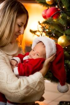 Portrait de mère et bébé en costume de père noël à cheminée
