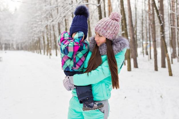 Portrait d'une mère et d'un bébé heureux dans le parc d'hiver