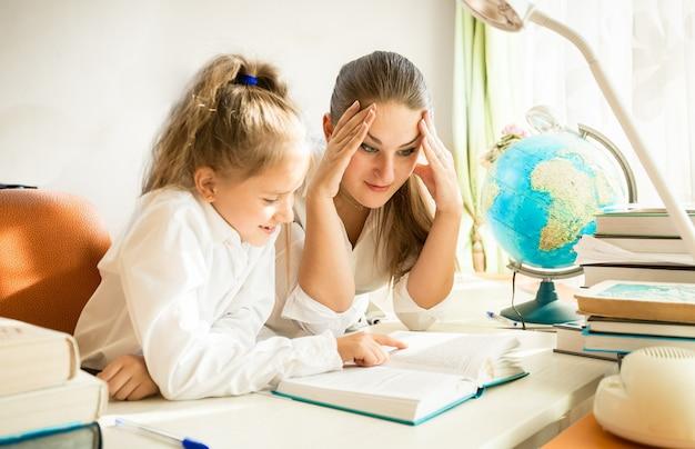 Portrait de mère confuse regardant les devoirs compliqués des filles