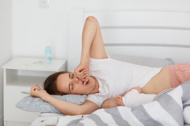 Portrait d'une mère fatiguée sans sommeil allongée avec une petite fille et bâillant, nourrissant son enfant, veut s'endormir, vêtue d'un t-shirt blanc de style décontracté, posant dans une pièce lumineuse à la maison.