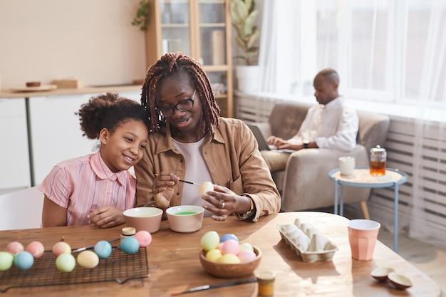 Portrait d'une mère et d'une fille afro-américaines aimantes peignant des œufs de pâques ensemble tout en étant assis à une table en bois dans un intérieur confortable et en profitant de l'art du bricolage, de l'espace de copie