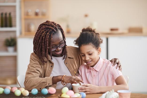 Portrait d'une mère et d'une fille afro-américaines aimantes peignant des œufs de pâques ensemble tout en étant assis à une table en bois dans un intérieur confortable et en profitant de l'art du bricolage
