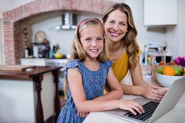 Portrait de mère et fille à l'aide d'un ordinateur portable dans la cuisine